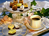 Petit fours on plate and cake platter and a cup of coffee