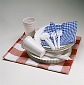 Paper plates, plastic cups & cutlery with napkins on cloth