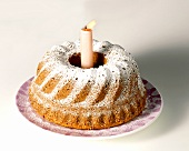 Fruit cake with icing sugar & burning candle for birthday