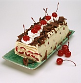 Loaf-shaped cherry ice cream cake, chocolate curls & cherries