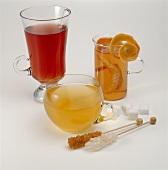Various teas in glasses; sugar crystals and sugar lumps