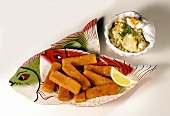 Fish kebab on fish plate and potato salad with egg