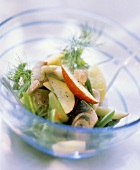 Herring salad with beans, apples and dill in glass bowl