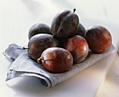 Several plums on blue fabric napkin