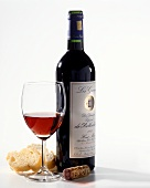 A bottle of red wine (Rothschild), red wine glass, white bread