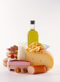High-calorie still life with cake, cheese, sausage, oil, cream