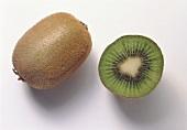 Whole and half kiwi fruit on white background