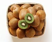 Lots of whole kiwi fruits & two kiwi fruit halves in basket
