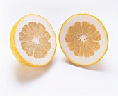 Two pomelo halves (cross-section) on white background