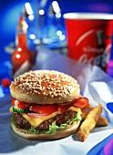 Cheeseburger mit Speck und zwei Pommes frites auf Papier