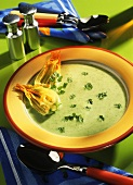 Courgette flower soup with chervil in yellow soup plate