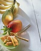 Slice of musk melon on plate, mango, papaya and bananas