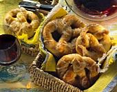 Cheese pretzels in bread basket, one pretzel beside it; wine