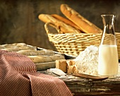 Still life with flour, yeast, milk, sugar and baguettes