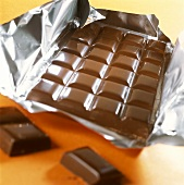 Schokoladentafel auf Silberpapier, davor zwei Stückchen