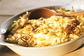 Cheese noodles (Spaetzle) with fried onion rings in baking dish