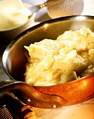 Mashed potato with pieces of butter in pan