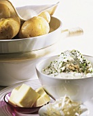 Potatoes in their skins in dish, chive quark & butter