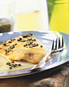 Oven-baked peppered fish with green peppercorns on plate