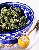 Sesam-Spinat in blau-weisser Schale auf Teller