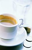 Espresso in white cup; coins, sugar lumps, glass