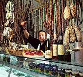Butcher with sausages & deli-goods in the shop (Provence)