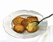 Potato rosti on white plate and apple puree on spoon