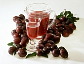 Plum juice in glass and jug surrounded by fresh plums