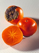 Two sharon fruits and a halved  fruit