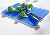 Broccoli florets on blue chopping board with knife