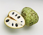 Cherimoya, whole and halved, on white background