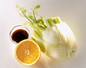 Fennel, half an orange and soy sauce in bowl