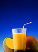 Mango juice in a glass with straw in front of two mangoes