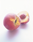 Peach and peach half on white background