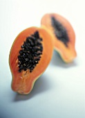 Two papaya halves on a pale blue background