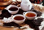 Three black teas in cups between tea leaves and crystal sugar