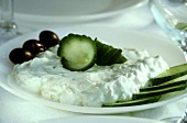 Tzaziki with sliced cucumber & olives on white plate