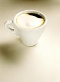 Caffè macchiato (with milk froth) in white espresso cup