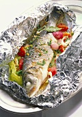 Loup de mer with vegetables in foil on platter