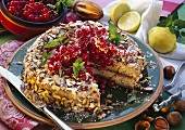Redcurrant and semolina cake with chopped nuts, a piece cut