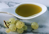 Grape seed oil on spoon beside green grapes on marble