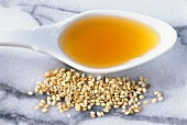 Sesame oil on spoon beside sesame seeds on marble