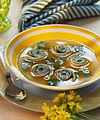 Vegetable broth with herb spirals and parsley leaves
