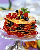 Layered pancakes with berries on glass plate