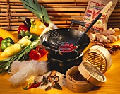 Still life with wok, bamboo steamer, vegetables, noodles, rice
