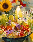 Mixed salad with flowers in a green dish