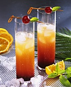 Tequila sunrise with ice cubes in two tall glasses