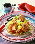 Deep-fried cheese balls with sesame crust on vegetable salad