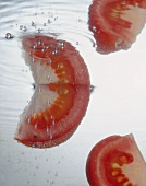 Tomato wedges falling into water