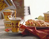 Pouring Hot Tea into Cup; Pastries